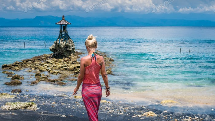 Women Walking Towards an Cute Temple on the Shore by the Sea on Nusa Penida with Dramatic Clouds