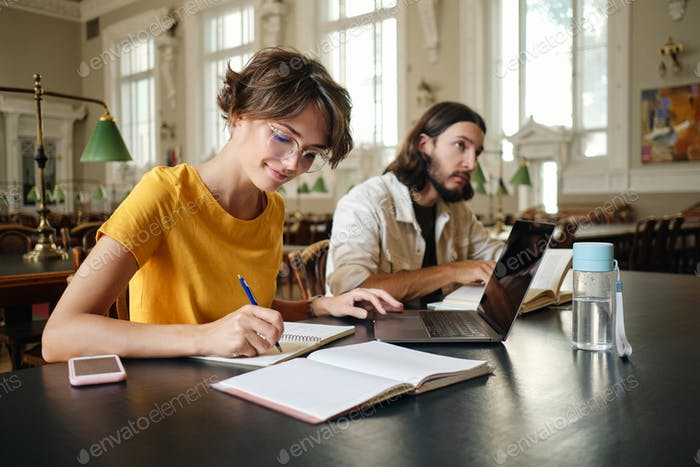Attractive smiling female student happily writing study notes with laptop in library of university
