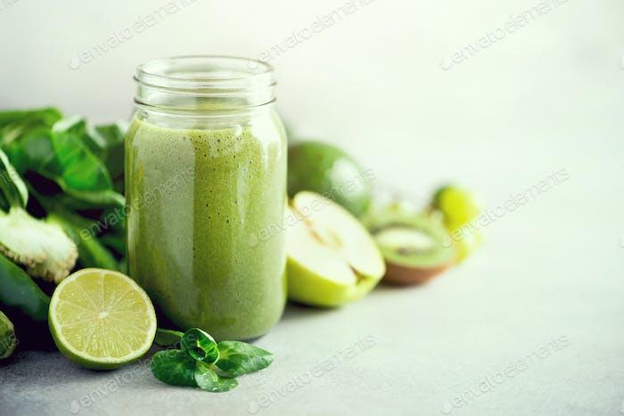 Glass jar mugs with green health smoothie, kale leaves, lime, apple, kiwi, grapes, banana, avocado