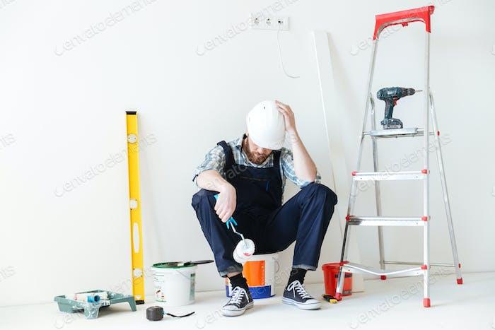 Young builder sleeping near repair equipment
