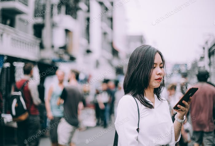 side view of a young woman playing mobile phone on the famous backpacker street Khao San in Bangkok