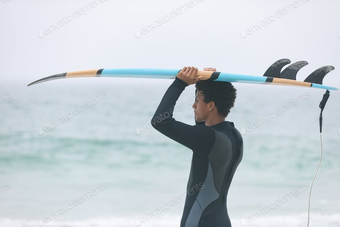 Side view of young mixed-race male surfer carrying surfboard on her head at beach