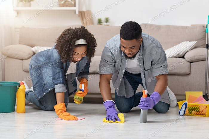 Black Married Couple Tidying Apartment Together, Washing Floor With Rags