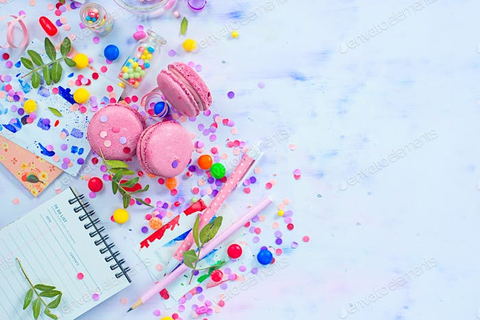 Party management and organization concept with sweets, confetti and an open notepad with blank pages