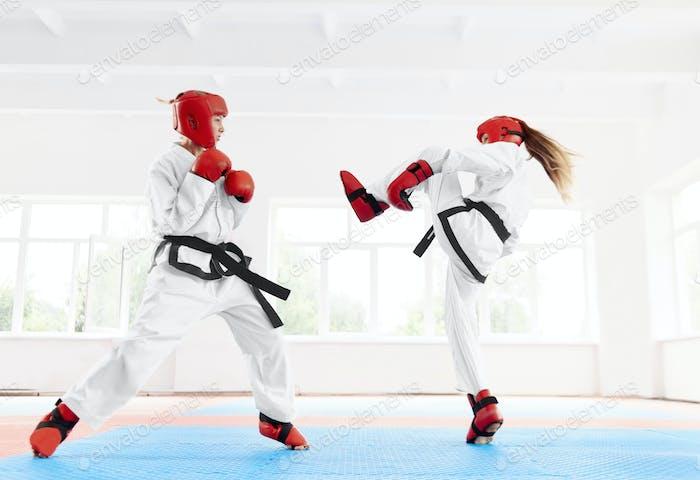 Zwei weibliche Kämpferin üben Karate Kick und Punch