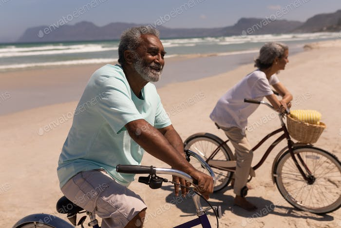 Happy senior couple standing with bicycle on beach in the sunshine with mountains in the background
