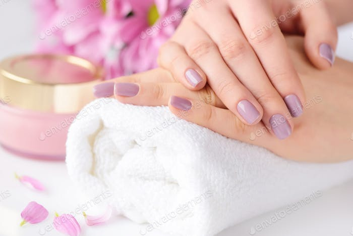 Women's hands with pink manicure are on a towel