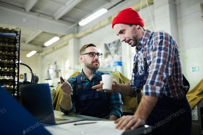 Two Mature Men Working at Factory