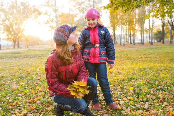 Cheerful and funny mother plays with yellow maple leaves