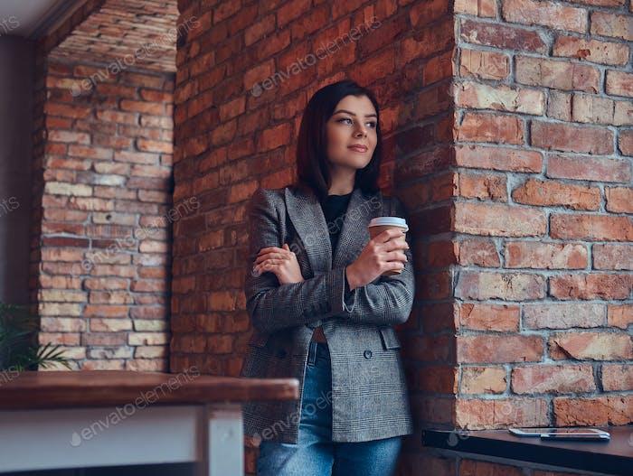 Портрет красотки бизнесвумен держит чашку утреннего кофе