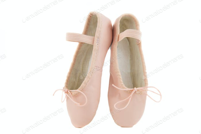 isolated pair of beginner ballerina shoes placed on tiptoes
