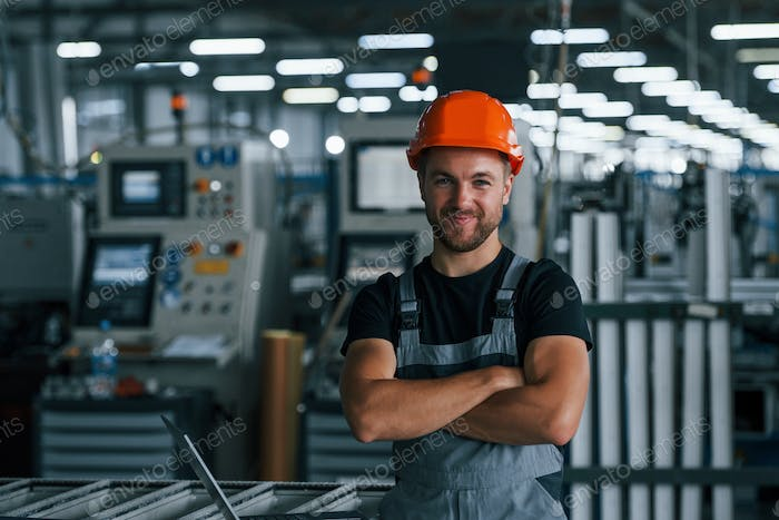 Portrait of industrial worker indoors in factory. Young technician with orange hard hat