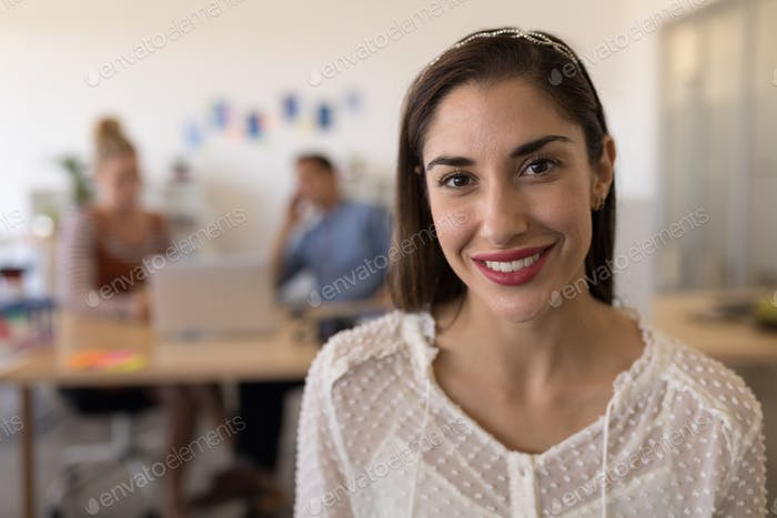 Portrait of beautiful happy Caucasian female executive smiling in modern office