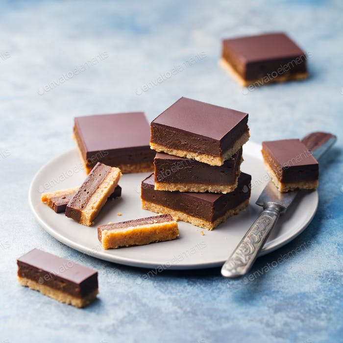 Chocolate Caramel Slices, Bars, Millionaires Shortbread on a Vintage Tray. Blue Background.