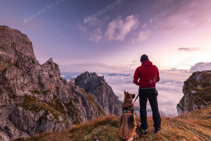 Adventure Man with Dog at High Mountains Peak at Sunrise. Togeth