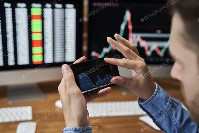 Young adult man analyzing the growth of stock market