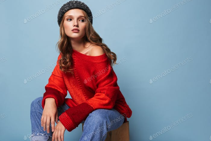Young attractive woman with wavy hair in hat and red sweater dreamily looking aside