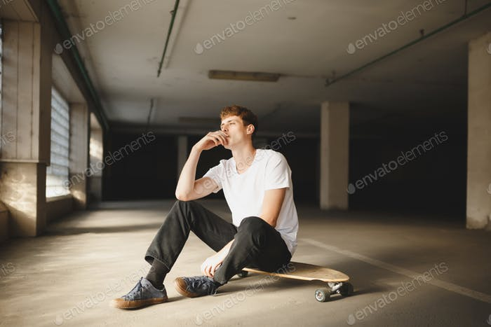 Cool boy with brown hair sitting on skateboard and smoking