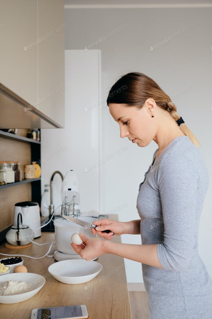 Woman breaks chicken eggs in a bowl in the kitchen.