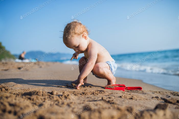 A small toddler girl sitting on beach on summer holiday, playing.