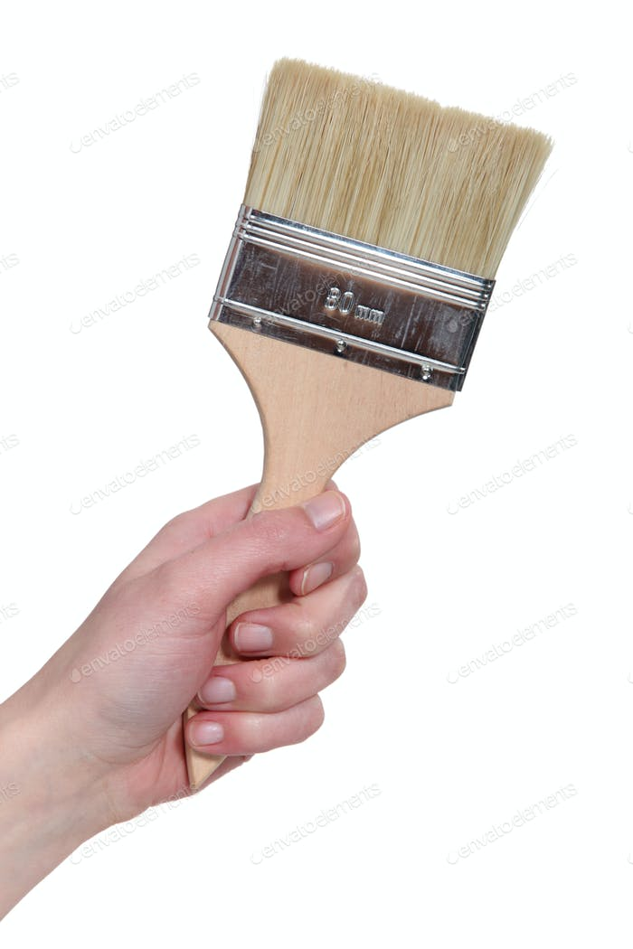 A hand holding a paint brush.