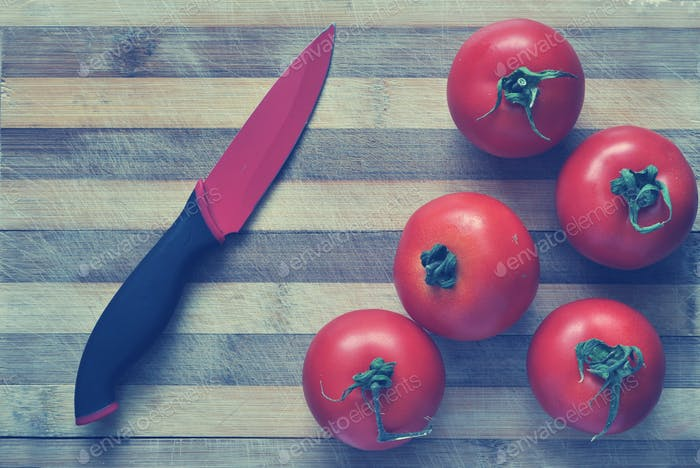 Red tomatoes and a knife on a cutting board. Toned