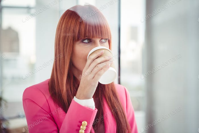 Portrait of a hipster businesswoman drinking a coffee cup in office