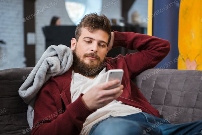 Relaxed young man lying on sofa and using cellphone