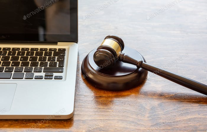 Judge gavel and a laptop, wooden background. Online auction concept