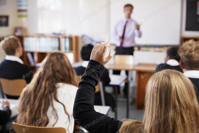 Female Student Raising Hand To Ask Question In Classroom