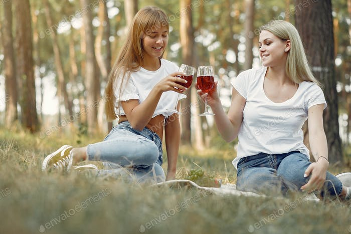 Girls sitting on a picnic and drinking vine