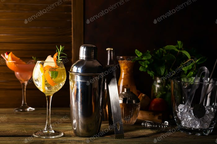 Cocktail shaker, swizzle, tongs and spoon with ice in a bucket for preparing a summer cocktail