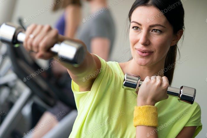 Happy fit fitness-mädchen trainieren indoor in fitness center