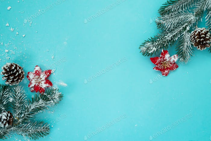 Christmas and New Year holidays background with snow fir tree and pine cones on blue background