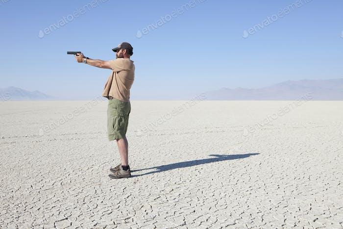 Ein Mann zielt auf eine Handpistole, hält sie mit ausgestrecktem Arm und steht in einer riesigen, kargen Wüste.
