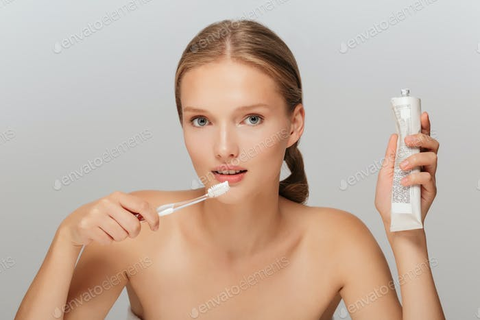 Portrait of young pretty lady without makeup holding toothpaste