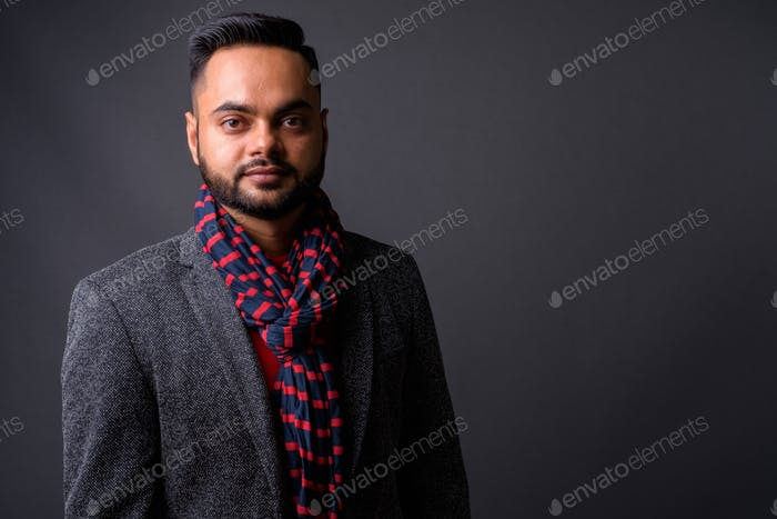 Young bearded Indian businessman against gray background