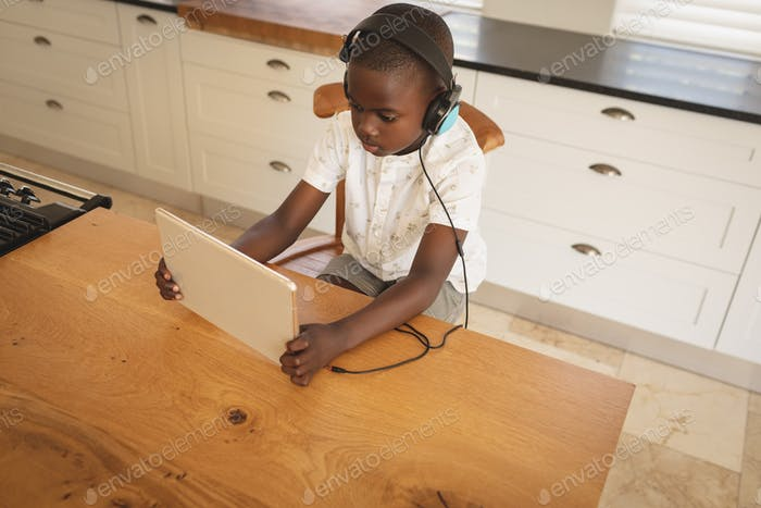 African American boy playing game on digital tablet at dining table in kitchen at home