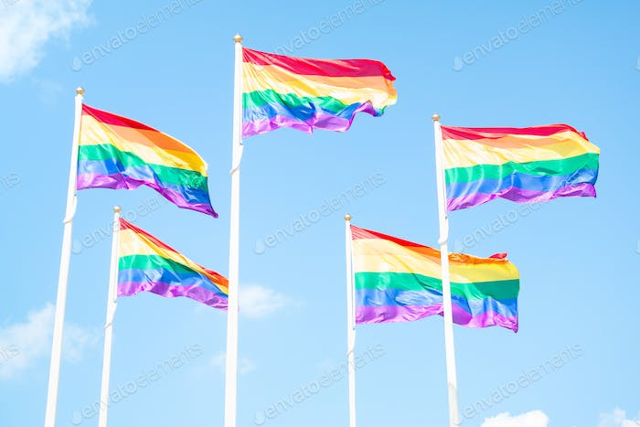 Rainbow LGBT flags waving on sky background with clouds, horizontal closeup