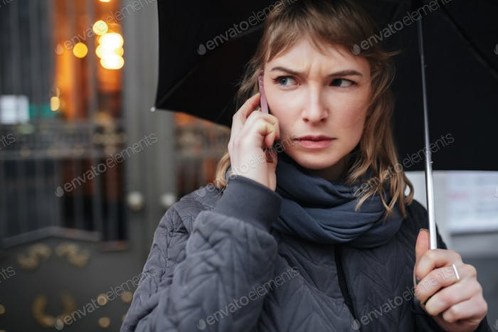 Portrait of woman standing on street with black umbrella and talking on her cellphone