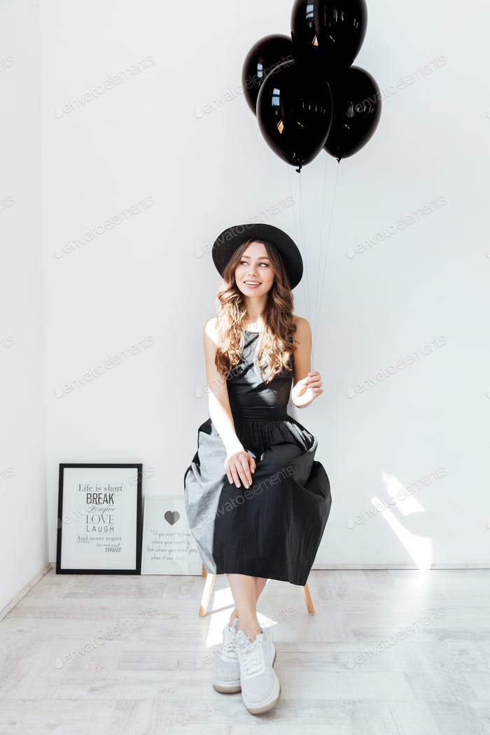Happy cute young woman sitting and holding black balloons