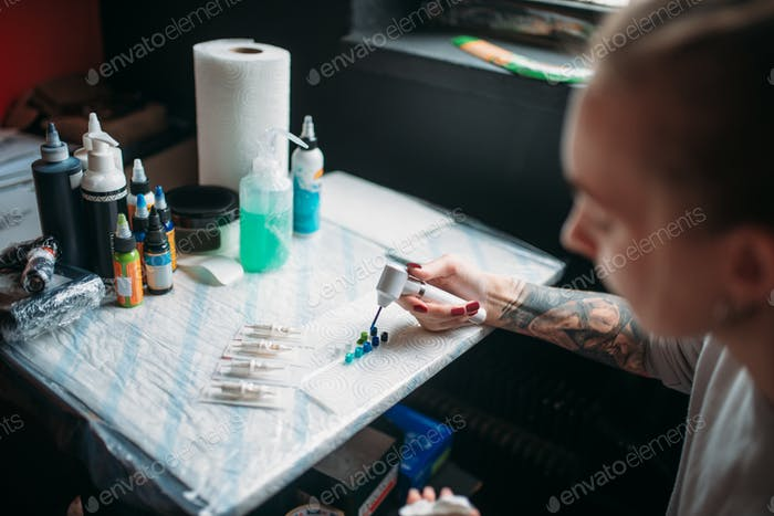 Female tattoo artist prepares color ink