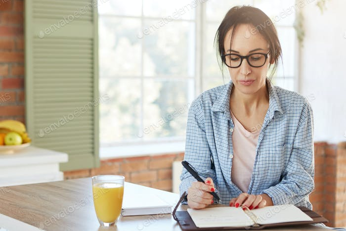 Indoor shot of serious European woman holds pen, writes information she found over internet or book