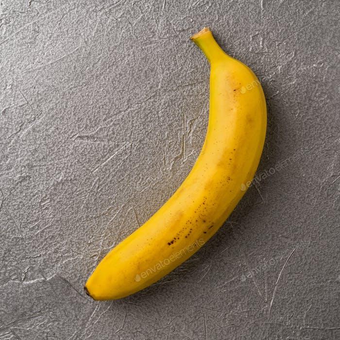 Simple image of single ripe yellow banana on gray metallic background