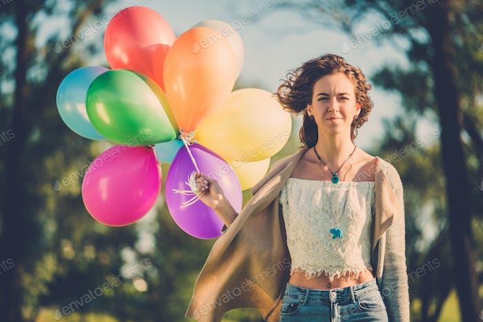 Mädchen mit regenbogenfarbenen Luftballons in einem Park.