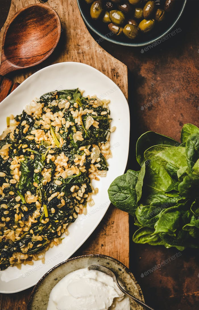 Flat-lay of Turkish traditional dish Bulgur and spinach on board