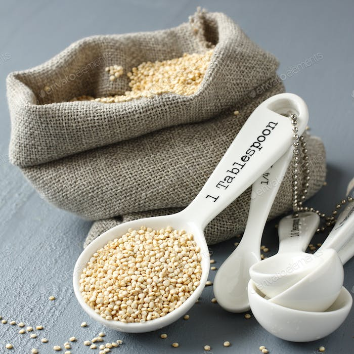 Quinoa grain in small burlap sack and porcelain measuring spoons