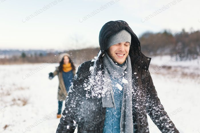 Cheerful couple playing snowballs in a snowy field in the winter