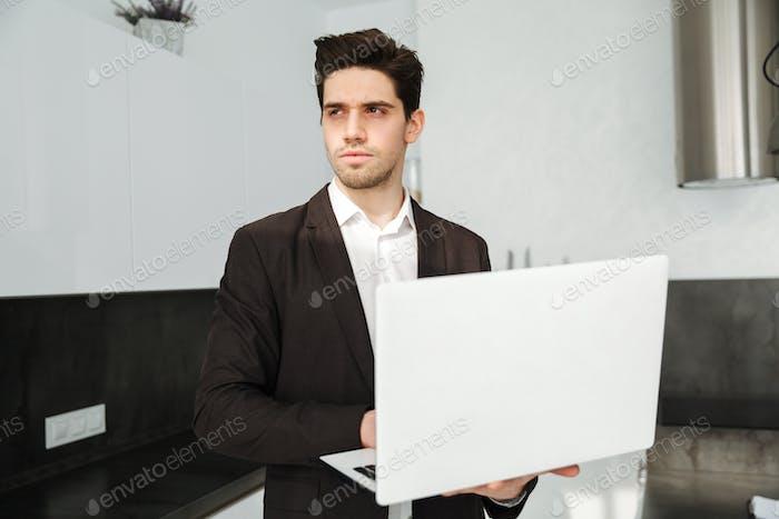 Serious young businessman using laptop computer.
