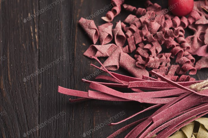 Assorted italian red pasta on wooden background